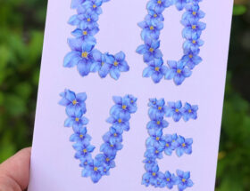 Hand holding a greeting card with the words LOVE made of purple painted flowers