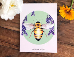 Greeting card with Bee illustration and Foxglove flowers sits on a country style wooden table, surrounded by flowers.